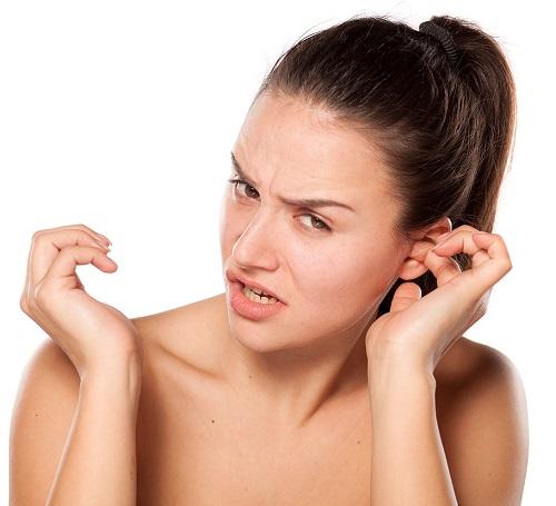 Женщина чешет в ухе